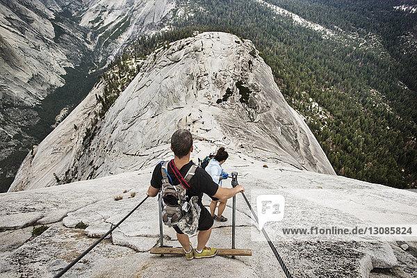 Wanderer  die von einer Felsformation im Yosemite-Nationalpark herunterkommen
