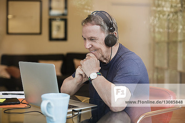 Happy senior man listening music while using laptop at home