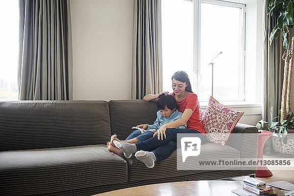 Mother sitting with son on sofa at home
