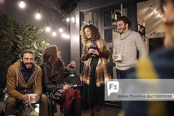 Freunde genießen Getränke bei einer Party im Hinterhof