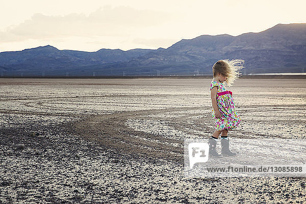 Side view of girl standing on arid landscape