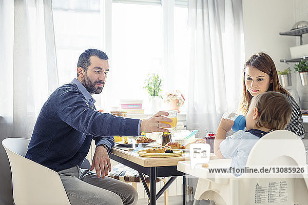Man offering juice to son while having breakfast at table
