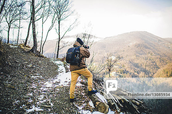 Rear view of hiker with backpack photographing while standing on mountain against sky