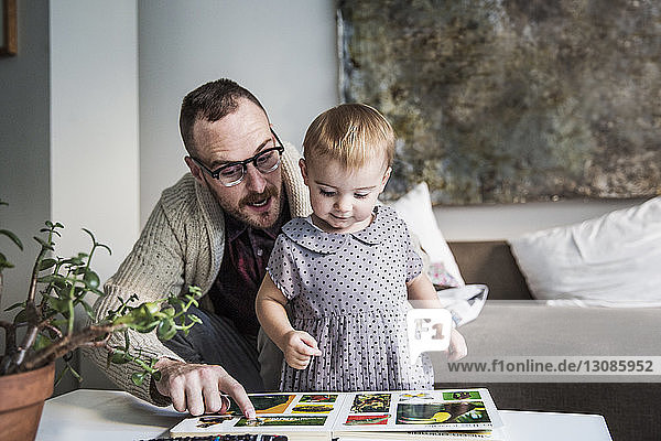Father reading picture book to daughter at home