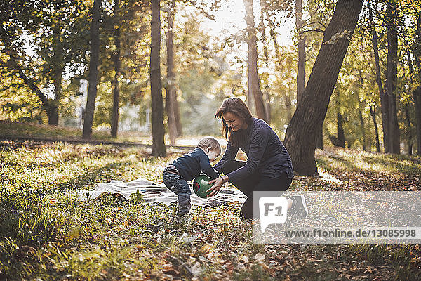 Mother and son playing with ball at park during autumn