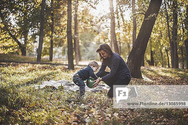 Mutter und Sohn spielen im Herbst im Park mit dem Ball