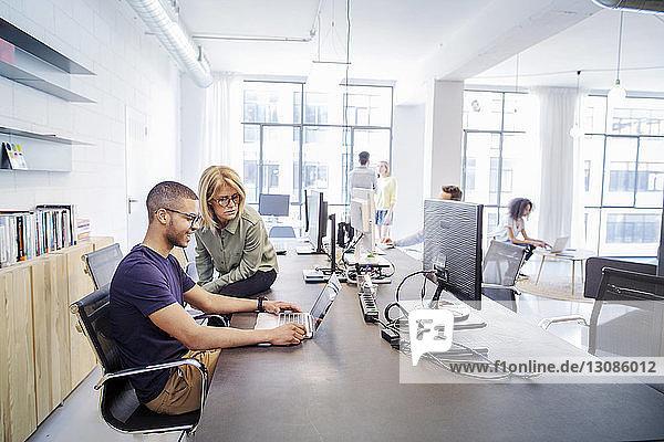 Geschäftsleute diskutieren bei Tisch im Büro