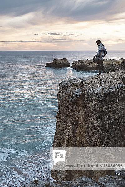 Mann schaut aufs Meer  während er bei Sonnenuntergang auf einer Klippe gegen den Himmel steht