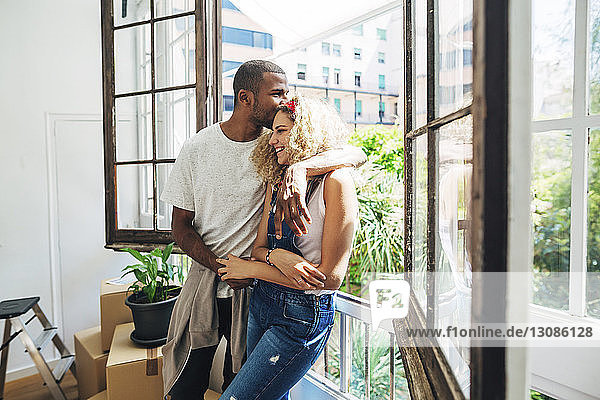 Husband kissing wife on forehead while standing by window in new house