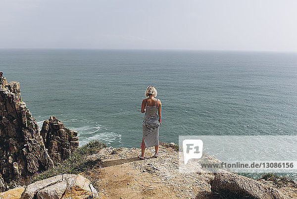Full length of woman looking at sea while standing on cliff