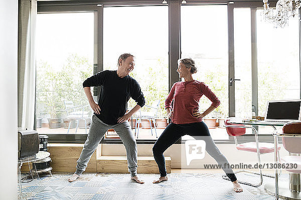 Happy senior couple exercising by window at home