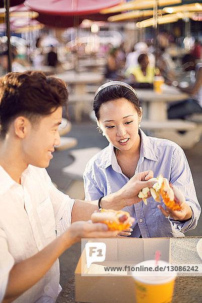Paar  das Hot Dogs isst  während es im Straßencafé sitzt