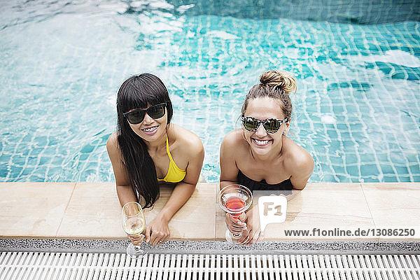Hochwinkelporträt glücklicher Freunde  die beim Entspannen im Schwimmbad Getränke halten