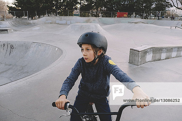 Boy wearing helmet while sitting on bicycle at skateboard park