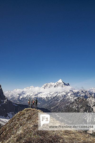 Wanderer stehen auf Berg vor klarem blauen Himmel