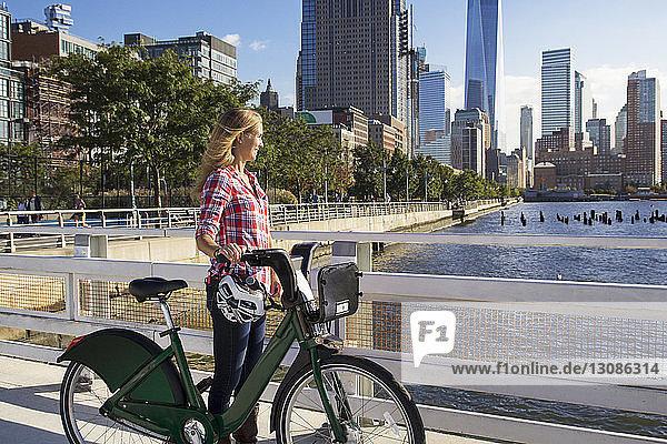 Nachdenkliche Frau mit Fahrrad auf der Brücke mit Blick auf Fluss gegen Stadt