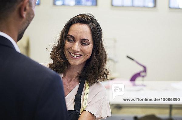 Lächelnder Modedesigner nimmt im Stehen am Workshop Maß an Geschäftsmann