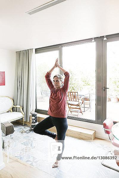 Reife Frau  die zu Hause Yoga in Baumstellung praktiziert