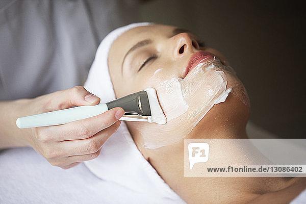 Weibliche Therapeutin  die im Spa eine Gesichtsmaske auf das Gesicht einer Frau aufträgt
