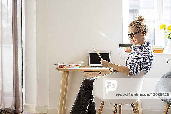 Woman reading paper while sitting on chair at home