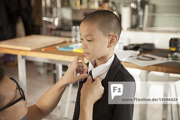Father adjusting son's necktie at home