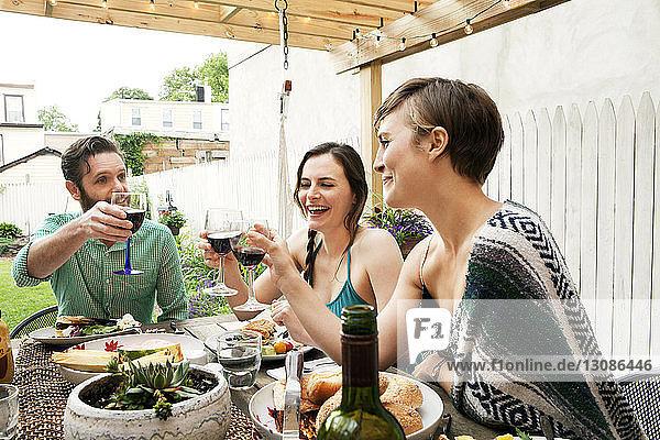 Freunde stoßen auf Weingläser an  während sie am Tisch im Hof sitzen