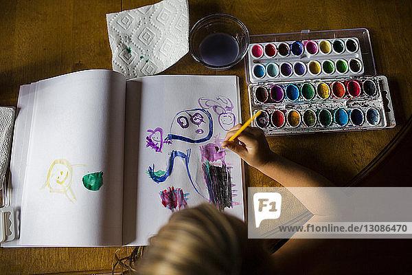 Hochwinkelansicht eines Mädchens  das in einem Buch zeichnet  während es am Tisch sitzt