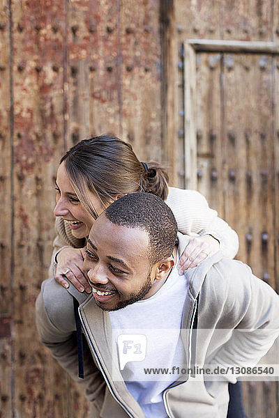 Happy man piggybacking woman against wall