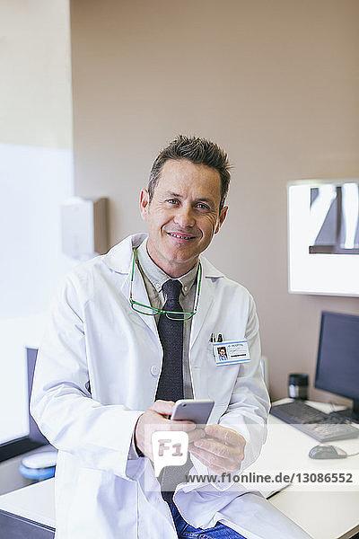 Porträt eines lächelnden Arztes  der ein Smartphone in der Hand hält  während er im Krankenhaus sitzt