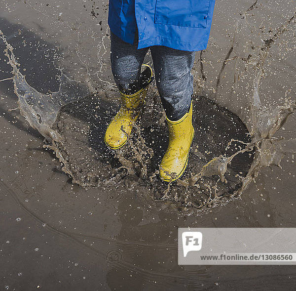 Low section of playful boy wearing rubber boots while splashing puddle