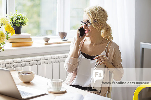Woman with breakfast talking on mobile phone at table