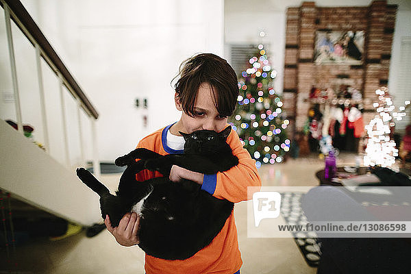 Boy kissing black cat while standing at home during Christmas