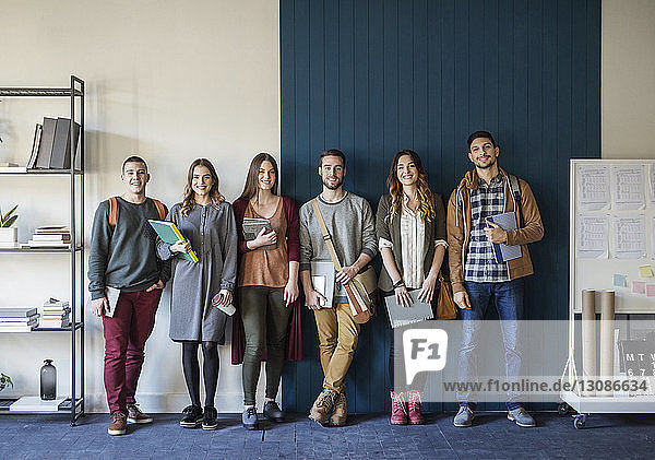 Portrait of friends standing against wall in classroom