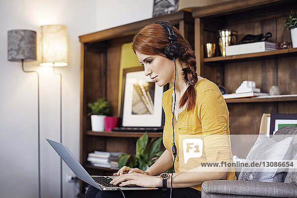 Side view of businesswoman wearing headphones while using laptop on chair