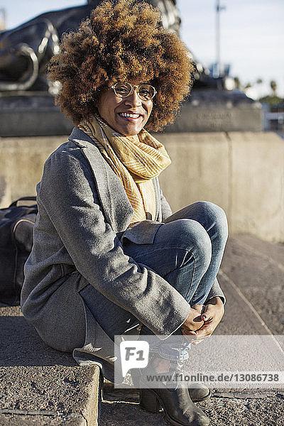 Porträt einer glücklichen Frau  die auf Stufen in der Stadt sitzt
