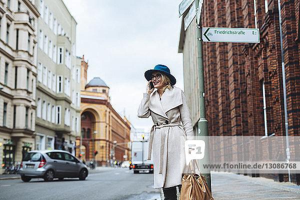 Glückliche Frau telefoniert mit einem Mobiltelefon  während sie auf der Straße in der Stadt steht