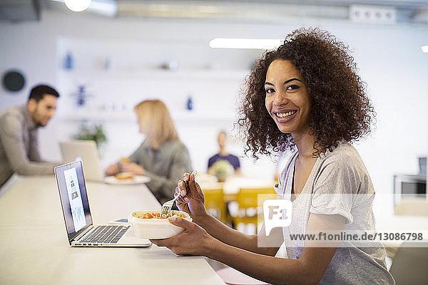 Porträt einer lächelnden Geschäftsfrau beim Mittagessen mit Kollegen im Hintergrund