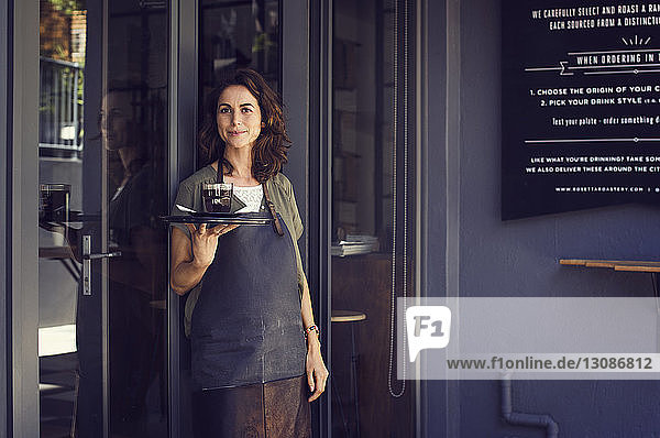 Porträt einer selbstbewussten Besitzerin  die vor dem Café ein Tablett mit Kaffeetasse hält