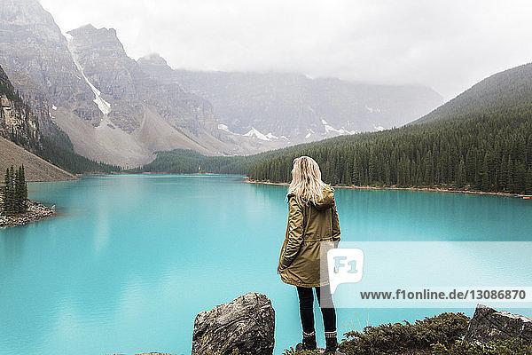 Rückansicht einer Wanderin mit der Hand in der Tasche  die am Moraine Lake vor den Bergen im Banff-Nationalpark steht