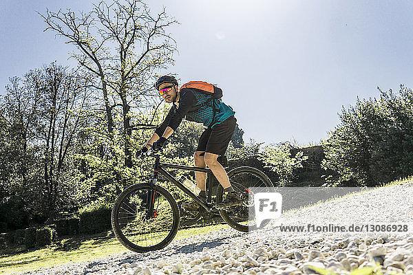 Mountainbike fahrender junger Mann in voller Länge am sonnigen Tag im Park