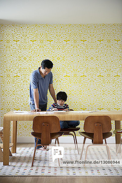 Father assisting boy with homework against wall at home