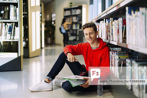 Porträt eines Mannes  der in der Bibliothek auf dem Boden sitzend studiert