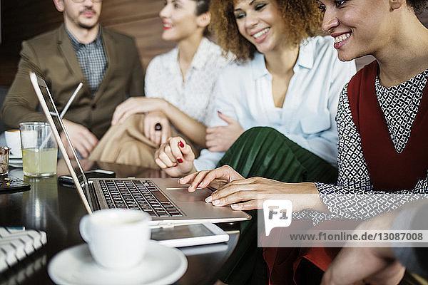 Geschäftsfrauen mit Laptop  während sie bei Kollegen im Restaurant sitzen