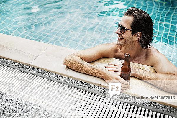 Hochwinkelansicht eines Mannes  der eine Bierflasche im Schwimmbad hält