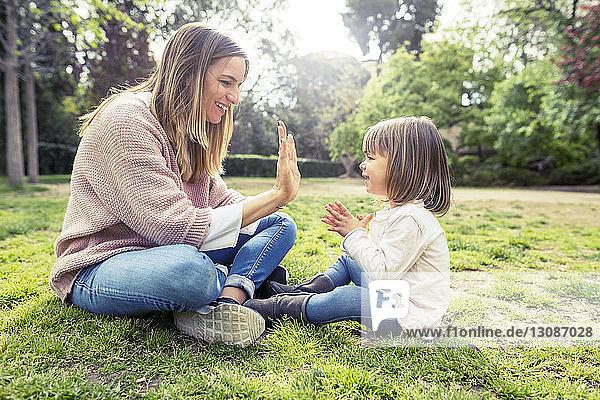 Seitenansicht einer glücklichen Mutter und Tochter beim Backen von Kuchen im Park