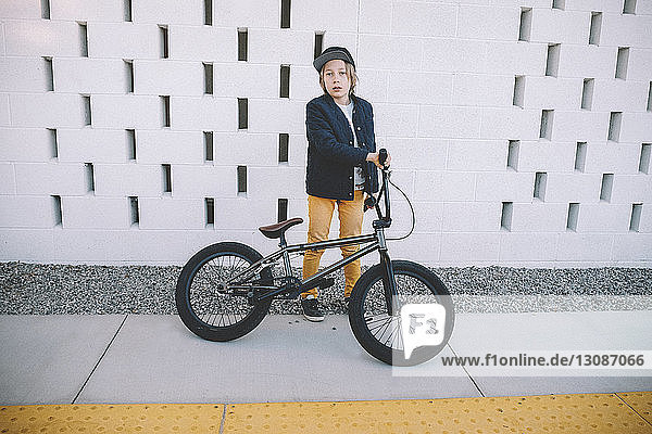 Full length portrait of boy with bicycle standing against wall in city