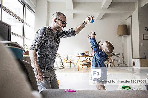 Happy father playing with daughter in living room at home