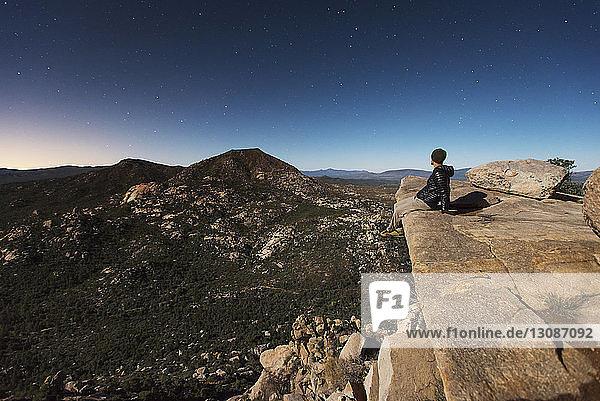 Wanderer sitzt auf Fels  während er in der Dämmerung die Berge gegen den Himmel schaut
