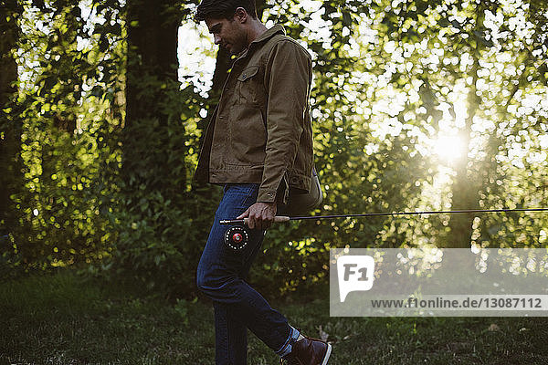 Side view of man holding fishing rod while walking in forest