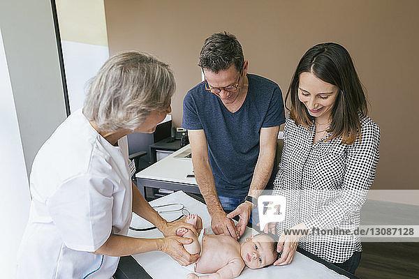Hochwinkelansicht des Arztes und der Eltern  die dem kleinen Jungen im Krankenhaus zur Seite stehen